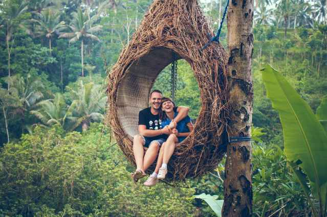 man and woman sitting on hanging chair by a tree